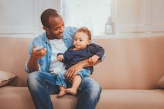 Delighted father babysitting his child. Our leisure. Alert loving daddy holding a remote control and babysitting his son stock photo