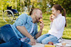 Delighted father and daughter eating sweet cakes Royalty Free Stock Photography