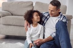 Delighted father and daughter sitting together. My daddy. Pretty inspired curly-haired girl smiling and looking at her daddy while sitting on the floor and Stock Photo