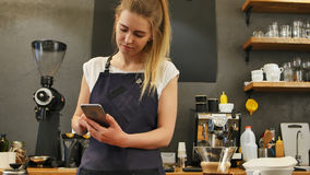 Delighted female barista using cell phone at work place. Close up. Professional shot in 4K resolution. 089. You can use it e.g. in your commercial video Royalty Free Stock Photos