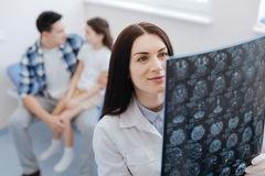 Delighted female doctor looking at the X ray scan image Stock Photos