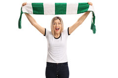 Delighted female football fan holding a scarf and cheering Royalty Free Stock Images