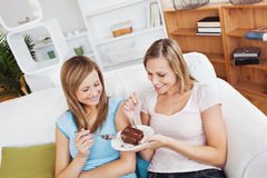Delighted friends eating a chocolate cake at home Stock Photo