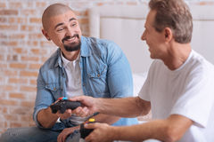 Delighted friends exchanging game consoles at home Stock Images