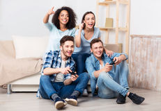 Delighted friends playing video games. Positive mood. Cheerful delighted smiling friends playing video games and expressing joy while spending free time together royalty free stock images