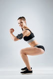 Delighted girl doing knee bands on a grey background Royalty Free Stock Images