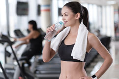 Delighted girl drinking water after training Royalty Free Stock Photography