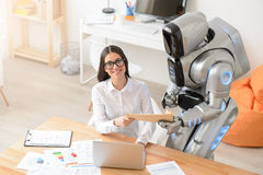 Delighted girl getting package from the robot Stock Image