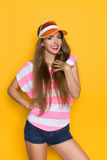 Delighted Girl WIth Hand On Chest. Close up of smiling young woman in pink stripped shirt and orange sun visor posing with hand on chest. Waist up studio shot on Stock Images