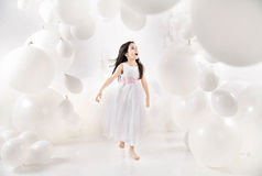 Delighted girl among numerous balloons Stock Photos