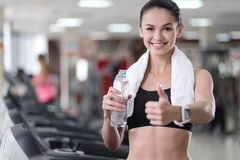 Delighted girl relaxing after training in a gym Stock Images