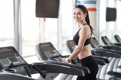 Delighted girl running on treadmill in a gym Stock Image