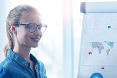 Delighted girl standing near board for demonstrating projects Royalty Free Stock Photo