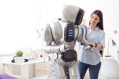 Delighted girl standing with robot Royalty Free Stock Image