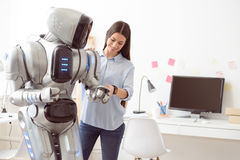 Delighted girl touching robot Royalty Free Stock Images