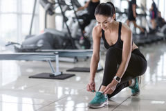 Delighted girl tying shoelaces in a gym Royalty Free Stock Photography
