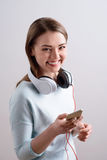 Delighted girl using smart phone. Time for rest. Cheerful delighted beautiful smiling girl holding mobile phone and listening to music while expressing gladness royalty free stock photo