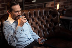 Delighted good looking man drinking alcohol Stock Image