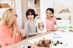 Delighted grandmother looks at drawings of grandchildren. Little boy drew owl on sheet. Girl painted landscape. Courses of fine arts stock photography