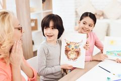 Delighted grandmother looks at drawings of grandchildren. Little boy drew owl on sheet. Girl painted landscape. Courses of fine arts royalty free stock image