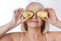 Delighted grey haired woman putting avocado halves to her eyes. Avocado facial mask. Delighted grey haired elderly woman standing against the white background Stock Images