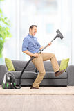 Delighted guy playing guitar on the vacuum cleaner. Delighted young guy playing guitar on the vacuum cleaner wand in front of a gray soda at home royalty free stock photography