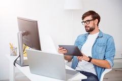 Delighted guy sitting and looking at his laptop Stock Photography