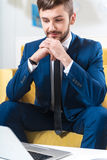 Delighted handsome businessman sitting on the couch Royalty Free Stock Photos