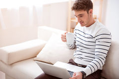 Delighted handsome man sitting on the sofa Royalty Free Stock Image