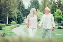 Delighted happy couple walking together in the park stock image