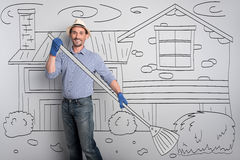 Delighted happy farmer cleaning the yard. Sweet home. Young good looking man smiling and holding broom while standing in the yard.y farmer cleaning the yard Stock Photos