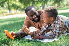 Delighted happy father and son talking about technology. New gadget. Delighted happy father and son lying on the grass while discussing modern technology royalty free stock photography