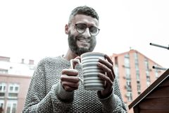 Delighted happy man wanting to drink his coffee. Hot coffee. Delighted happy man looking into his cup while wanting to drink his coffee stock photography