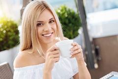 Delighted happy woman enjoying her drink. Pleasant morning. Delighted happy attractive woman holding a cup of tea and enjoying her drink while having breakfast Stock Image