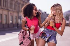 Delighted happy women trying each others drinks stock photography