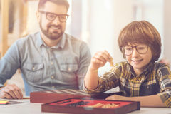 Delighted intelligent boy holding a chess piece. Chess game. Delighted intelligent positive boy holding a chess piece and looking at it while sitting with his Stock Photos