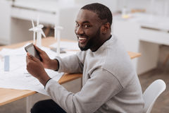 Delighted joyful man having a tablet in his hands. Age of igeneration. Delighted joyful positive man having a tablet in his hands and smiling while using modern Stock Photos