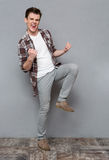 Delighted joyful young man dancing and smiling Stock Images