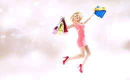 Delighted jumping lady with shopping bags Stock Photos