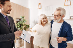 Delighted lawyer offering contract to aged couple of clients royalty free stock images