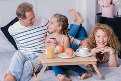 Delighted little girl holding berry cupcake with her grandparents Royalty Free Stock Image