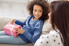 Delighted little girl holding her gift. Great childhood. Pretty content curly-haired girl smiling and holding her gift while looking at her mother sitting near Royalty Free Stock Photos