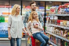 Delighted little girl sitting on a shopping cart. And choosing candy with her parents at the supermarket Stock Image