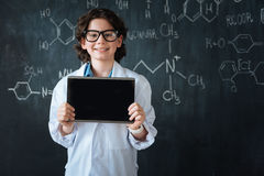 Delighted little scientist enjoying modern technologies in the laboratory. Using modern technologies. Brainy smiling glad researcher standing near the blackboard Royalty Free Stock Photos