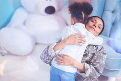 Delighted loving mother hugging her daughter stock images