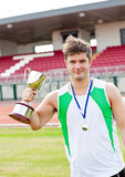 Delighted male athlete holding a cup and a medal. Standing in a stadium Stock Photos