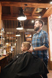 Delighted male barber standing behind his client Royalty Free Stock Photos