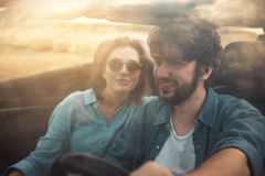 Delighted male and female are having journey abroad. Our best vacation. Through glass view of pleasant young boyfriend and girlfriend are going by car to summer Royalty Free Stock Image
