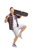 Delighted male skater gesturing happiness. Full length portrait of a delighted male skater holding a skateboard and gesturing happiness isolated on white Royalty Free Stock Image