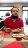 Delighted man / customer in red shirt eating Chinese / Japanese food in a restaurant.  Stock Photos